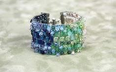 Ce projet ajoute de la fantaisie dans la rigidité du métier à tisser. Alternez différentes tailles de perles et composez un dégradé de couleurs. #MétieràTisser #Tissage #Bijou #Bijoux #Creation #Perle #Bille #Beads #Jewelry #Jewel #Bracelet #BeadLoom #Handmade #Craft #DIY #Create #Workshop Cliquez pour voir les dates d'atelier disponible! Cuff Bracelets, Craft, Creations, 2013, Beadwork, Dates, Jewelry, Bling, Budget
