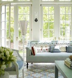 the tufted sofa with spindle legs, the Moroccan inspired patterned rug, the cane chair, the wall sconce, the patio doors with all those windows and the color scheme come together gorgeously in this family room!