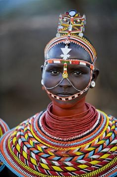 This folk dress is typical of the Samburu people of East Africa which means butterfly. In these tribes girls would receive strands of loose beads from admirers. The ideal amount would support a girls chin. By 15-16 a girl should have collected enough for a marriage proposal. Males were also just as decorative as girls.