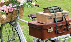 Jardim com bicicleta vintage. Bicicleta com cestinha. Cesta de flores na bicicleta. Malas antigas.