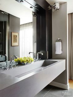 A trough-style vanity creates a spa-like focal point in this modern bathroom. A clean-lined upper cabinet adds just enough storage space to hide away bath essentials. Two faucets provide double function in the streamlined sink.