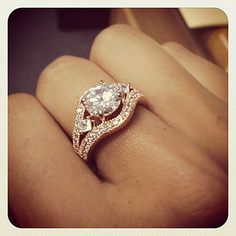 @: Rose Gold plated Ring featuring a brilliant cut CZ. This ring truly dazzles with two princess cut DZ diamonds flanking a larger center stone and two rows of CZs.