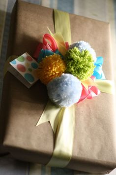 craft paper, ribbons, and yarn pom poms baby shower gift wrap idea