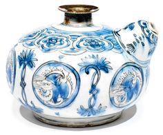 KENDI SAFAVIDE Base de narguilé en céramique à décor bleu-blanc à la chinoise, ornée de dragons stylisés dans des médaillons alternant avec des motifs floraux. Autour du col, une frise de médaillons polylobés floraux. Le haut du col fracturé est muni d'une monture en métal. Marque chinoise apocryphe sous la base. Restaurations au talon et partie supérieure du col manquante. Iran safavide, Kirman ou Meched, XVIIe siècle. HAUT. 12,5 cm (4,9 cm)