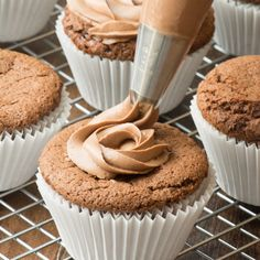 Nutella buttercream being piped onto a Nutella cupcake.