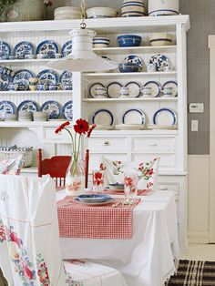 Traditional Country-Style ~ The dining room hutch offers abundant storage options for linens, silverware, and the homeowner's collection of blue-and-white dishes. The table is covered in a bright white table cloth with red gingham placemats. Vintage floral sheets become delightful chair covers. A cozy rag rug covers the floor.