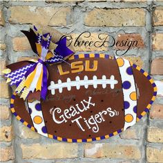 """Who's ready for some Tiger football??      Our LSU football door hanger is made from 1/8"""" plywood, and measures 20"""" Wide x 12"""" High. The back is painted solid black and it is finished with 3 coats of exterior sealer. Each one comes ready to hang with a wire hanger (not included in measurements) a..."""