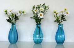 3 Turquiose Glass Bottles with daisies image Glass Bottles, Glass Vase, Daisies, Artificial Flowers, Silk Flowers, Shades Of Blue, Wedding Flowers, Image, Home Decor