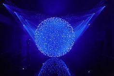 """Titulo de la obra: """"FLUIDIC Sculpture In Motion"""" Nombre del autor: Christopher M. Bauder, WHITEvoid  Reseña: 12 mil pequeñas esferas luminosas, con lásers de alta velocidad y la interacción de los visitantes, dieron vida a esta obra, responde a los movimientos que se perciben en el ambiente  mezclando las curvas de la naturaleza con las formas propias de las esculturas humanas para crear formas orgánicas, originales y dinámicas. Enlace: https://www.youtube.com/watch?v=yQ3vqfdIToo"""