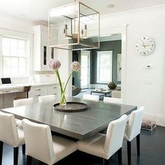 Perfect Chic Dining Room Features A Glass And Metal Lantern Illuminating An  Oversized Gray Square Dining Table Lined With Eight White Dining Chairs  Situated Across ... Part 23