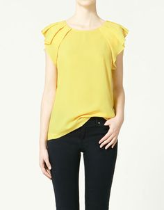 Yellow top with pleats at shoulders.