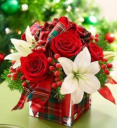 All Wrapped Up™ for the Holidays  Send a holiday present with real presence: a fresh bouquet of red roses, white lilies, hypericum and assorted fragrant Christmas greens. Hand-designed by our florists in a modern glass cube vase, it's a festive surprise for holiday hostesses, winter birthdays or anniversaries.