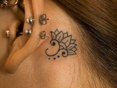 Beautiful elegant small black-ink lotus flower tattoo behind ear