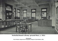 """Yorkville interior. This photo likely taken before 1909, when the Toronto Public Library Board had adopted the """"open shelf"""" storage system, which allowed readers to browse the books and not have to request them from staff. The area to the right of the main entrance was set aside as the """"Teachers and Children's Room."""" The branch was finished throughout with massive quarter-cut oak. Note the light sconces on the upper right: two of these were uncovered in May 2003 during a retrofit at the…"""