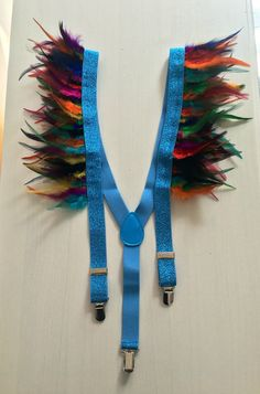 Strap in and Check out in these colorful suspenders. Easy Clips for use on your choice of bottoms. Unisex - Made for him but beautiful on her too! Metallic baby blue elastic suspenders (bracers) with multicolor feathers  One Size Fits all Handmade in London  Check my store out for other colors!   If this inspired you but you would like something custom please message me!  CUSTOMERS NOT LOCATED IN THE EUROPEAN UNION: PLEASE USE PROMO CODE: GLITTER FOR A 20% DISCOUNT!!!!  Shipping Disclaimer…