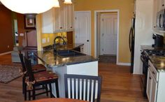 Adorable kitchen with granite countertops and yellow walls from Sciortino Developers!