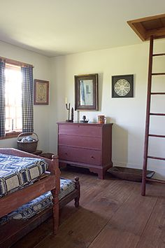 "This bedroom, which the couple refers to as the ""Hired Man's Room"" is furnished with an early matching low-post bedstead and early trundle b..."