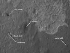 """""""The four main pieces of hardware that arrived on Mars with NASA's Curiosity rover were spotted by NASA's Mars Reconnaissance Orbiter (MRO). The High-Resolution Imaging Science Experiment (HiRISE) camera captured this image about 24 hours after landing."""" The dark areas are not scorching as you might think, but places where the bright dust has been blown away, revealing darker rock beneath, including the darker area around the lander."""