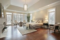 Master bedroom in new construction home with tray ceiling, wood floors and fireplace