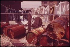 Original Caption:Rusty Oil Cans Pile Up near Home in Broad Channel, a Jamaica Bay Community with Numerous Pollution Problems  Date:1973. Photo: NARA