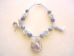This bracelet was a custom order for a friend of a friend who likes cowboy / cowgirl things (lives in Wyoming and owns her own horses!), and was hand-crafted from light blue glass, natural blue and white sodalite, engraved silver-plated flowers and 3 x Western charms - horse with horseshoe, cantering horse and cowboy boot.   It was sold as part of an animal rescue fundraiser - 50% of the profits go to the animals!  Want to sell bracelets like these for your own charity? Just drop me a line…