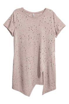T-shirt à l'aspect usé: T-shirt long en jersey souple et ajouré. Modèle à manches courtes avec détail croisé cousu devant et base asymétrique.