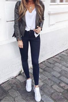 a women wearing a casual fall outfit with a t shirt green leather jacket dark blue skinny jeans and white sneakers