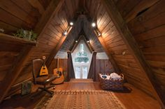 Cozy A-Frame Cabin in the Redwoods. Bedroom, facing the stairs + the front door. Wood floors. Throw rug. California