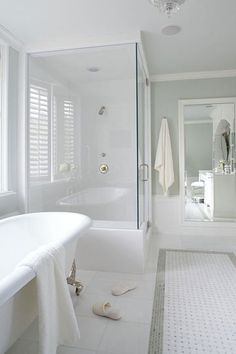 The designer wanted the shower to take advantage of light from the bath's big bay window and have the appearance of a frameless walk-in enclosure. Clear-glass partitions keep in heat and steam without spoiling the open feeling. The shower walls and base are white marble like the perimeter floor tiles.