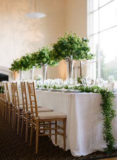 Wedding Reception With Long Tables: Centerpiece with Viburnum in trumpet vases and greenery garland.