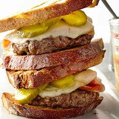 Cuban Burgers -  Take your taste buds on a trip to Cuba with our juicy burger recipe that's piled high with pickles, Fontina cheese, and  onion, then slathered with our homemade mojo sauce, a traditional Cuban spread that adds a kick of tangy garlic and citrus flavor. Cuban Burgers Makes: 4 servings Prep: 25 mins Cook: 5 mins Grill: 14 mins