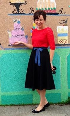 bright pink 3/4 sleeve sweater, black knee length waist high full a line skirt, blue ribbon sash thin waist belt, black flats bow