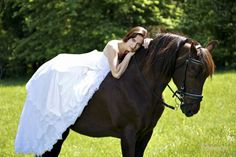 Bridal portrait with a black horse in the grass.