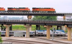 https://flic.kr/p/u2Mvjr | Low Speed Chase in KC | Slow Speed Race: In a chase that would embarrass OJ Simpson, an eastbound BNSF intermodal train rolls down the flyover as Amtrak's train 311/316 (anyone want to claim what number it is at this point?) lumbers back towards Union Station after turning itself at BN Crossing.   Combined speed of the two trains at this point was possibly 20 mph.