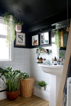 Black boho glam bathroom with plants and wood and gold accents