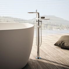 """For free-standing baths the collection offers a floor-mounted mixer complete with a hand shower. The handle and shelf are made from DuPont ™ Corian® and are therefore a natural choice for """"solid surface"""" baths. Corian, Solid Surface, Bathroom Furniture, Bathtub, Shelves, Flooring, Shower, Mixers, Design"""