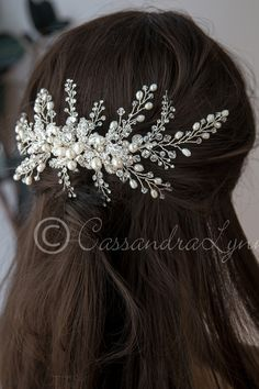 This stunning bridal hair comb is sure to garner attention on your special day! The center is a cluster of rhinestone covered leaves, ivory glass pearls, freshwater pearls, Swarovski crystal beads and round rhinestone jewels. Sprays of more crystal beads and freshwater pearls, as well as sprays of round rhinestone radiate out to be woven into your bridal hair style. On a metal or could also go on an alligator style clip.  It is about 8.5 inches long and 4.25 inches high.