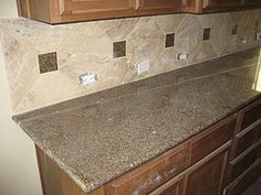 Kitchen backsplash made of small accent tiles in combination with large  tiles with simple design