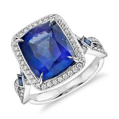 Blue Nile. Truly unique, this gemstone ring features a 6.17ct cushion-shaped tanzanite surrounded by sparkling micropavé-set diamonds and accented with blue sapphire set in 18k white gold. (=)