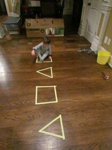 Wy and I had a busy new year's night trying all kinds of fun art activities but it was also nice just to do something geared more towards using our large motor skills… I started us off by making some shapes with yellow painter's tape on the floor. Painter's tape is always better than masking …