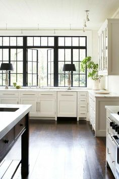 Love this bright white open kitchen with huge paneled windows, statuesque table lamps on either side of the basin kitchen sink, straight bar drawer pulls and dark wood table serving as the marble topped kitchen island.