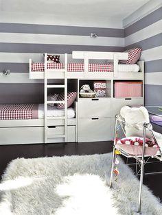 La ropa de cama de color rojo contrasta con el gris de las paredes y literas