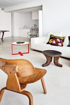 África libre - AD España, © manolo yllera Junto a la pared que divide el salón de la cocina, sofá con chaise-longue George de Antonio Citterio para B&B Italia con cojines realizados con telas de bubus senegalesas.