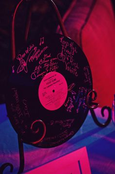 Guests sign a record for a guest book. It would be super cute if it was of the first song