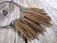 Made of Genuine brown leather. Leather and teal beads make up the tribal look of this sweet necklace. You can wear it long or short, just slip it over your head and adjust to the length that looks best on you. The leather and ceramic beads are strung on brown suede cording. Thank you for stopping by. Have a great day.