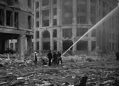 Firemen spray water on damaged buildings, near London Bridge, in the City of London on September 9, 1940, after a recent set of weekend air raids. (AP Photo)