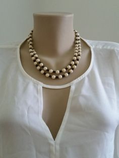 This beautiful black, white and gold-colored vintage double strand necklace and clip on earrings set looks great for both daytime and evening. This costume jewelry necklace will fall to the collarbone on most women. Likely from the late 1950s or early 1960s.