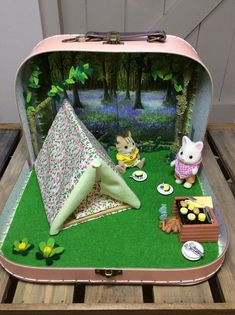 A beautiful hand made playset featuring a bluebell woodland setting with trees, flowers and felt grass. Complete with Sylvanian Families Camping Set with one additional character in a Sass and Belle pale pink suitcase ( 10 x 7 by 3 deep) . In addition I have made a little BBQ camp