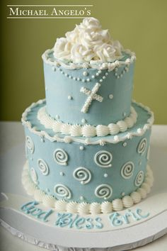 Holy Rosary with Swirls #30Religious This cake is iced in blue buttercream and accented with white swirls and polka dots. It is a very popular design for any religious celebration. The top tier has a bed of roses with a rosary that is piped on. The colors can be changed to match your event.