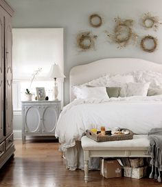 Love the light, neutral colors and the wreaths above the headboard